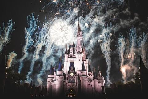 闇の中盛大に打ち上げられる花火で照らされるディズニーランドのシンデレラ城