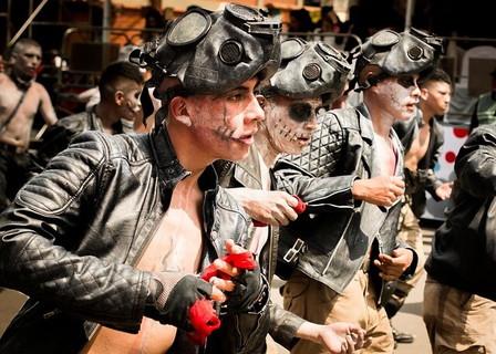 思い思いの仮装をして道を歩くパレードに参加する男性たち