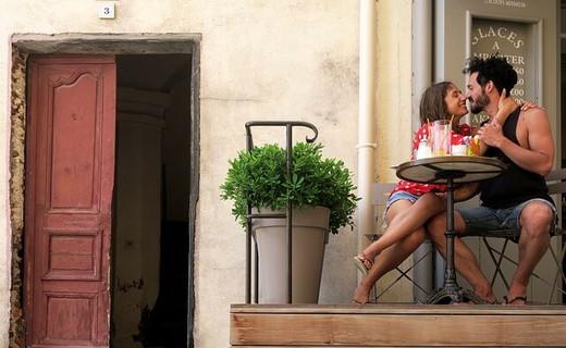 カフェテーブルに腰かけ話をしているうちに意気投合してキスをする男女