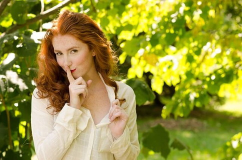木漏れ日の中で唇に人差し指を当てて微笑む白いシャツを着た柔らかい雰囲気の女性