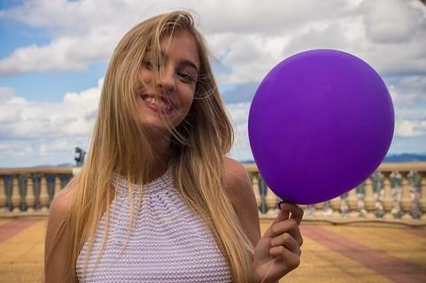 青空の中、紫色の風船を片手に自然体で微笑む親しみやすい雰囲気の女性