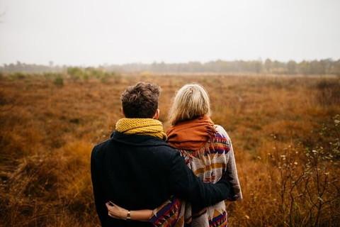 コートにマフラーを巻きずっと先まで続く草原を眺めるカップルの後ろ姿