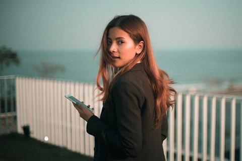 スマートフォンを持って微笑みながら振り返るロングヘアーの女の子