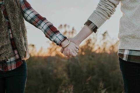 夕焼けの中しっかりと手を握り合う信頼関係をしっかりと築いた2人