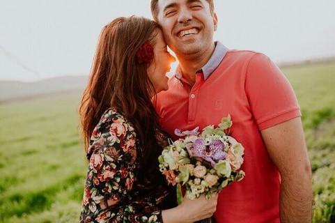 花束を持って顔を寄せる女性を抱き寄せ幸せそうに微笑む男性