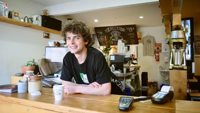 カウンターキッチンにもたれかかり爽やかに微笑む男性