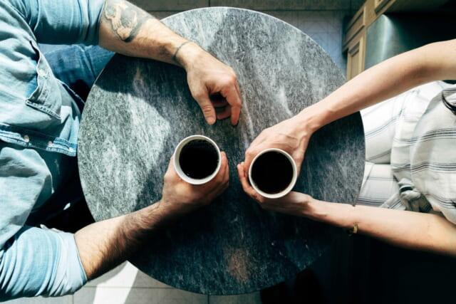 小さなテーブルを挟んで向かい合いコーヒーを飲みながら話し込むカップル