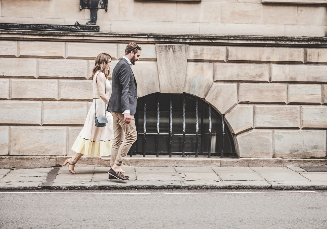 完璧なスタイリングで女性の手を取りエスコートしながら歩く余裕のある紳士