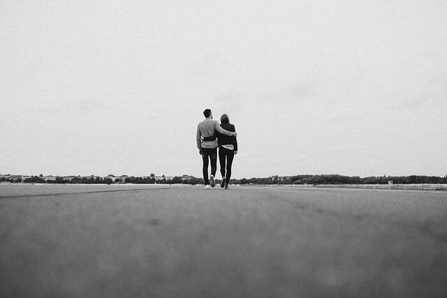 肩を寄せ合い地平線まで続く道を歩いてゆく仲良しカップル