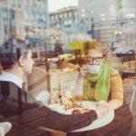 カフェのテーブル席で向かい合って座り恥ずかしそうに顔をそむける女性とそれを見つめる男性