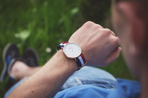 腕時計で時間を確認しながら行動する男性