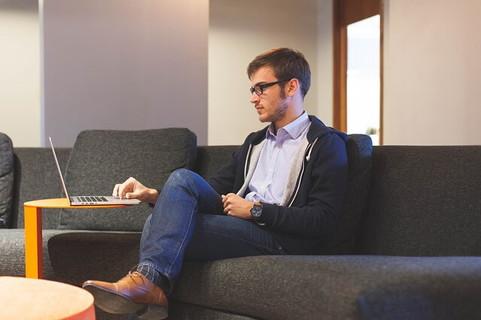 自宅のソファに座りラップトップで情報収集しながらデートプラン立てる男性