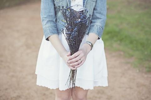 白いワンピースにデニムジャケットを羽織り、青い花束を持つ女性