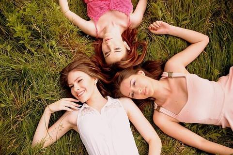緑の中に寝転がる若々しく魅力的な3人の女性