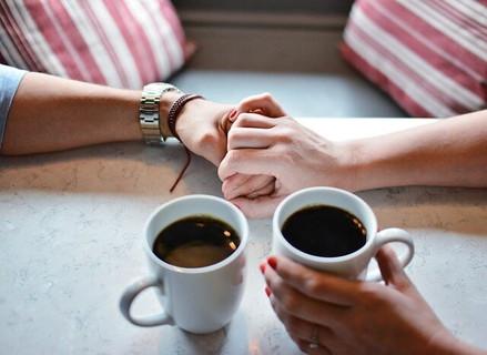 コーヒーを飲みながらテーブルの上でギュッと手を握り合うカップル
