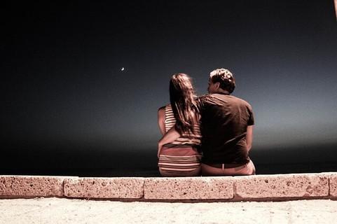 夜空が広がる中、女性の腰に手を回し親密に話をするカップル