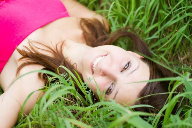 草むらに寝転がり白い歯を見せて微笑む清潔感あふれる女性
