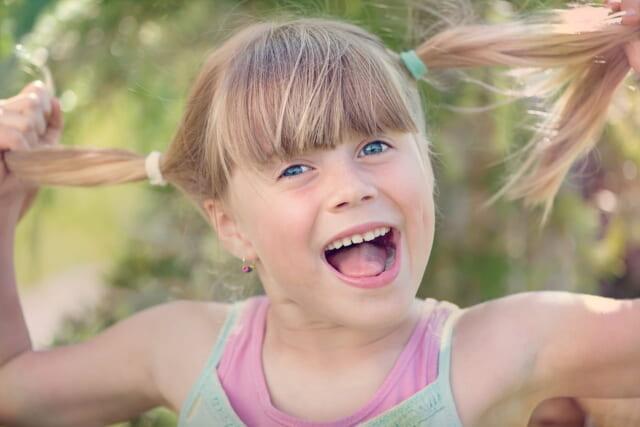 ツインテールを両手でつかみ笑顔で飛び跳ねる明るい女の子