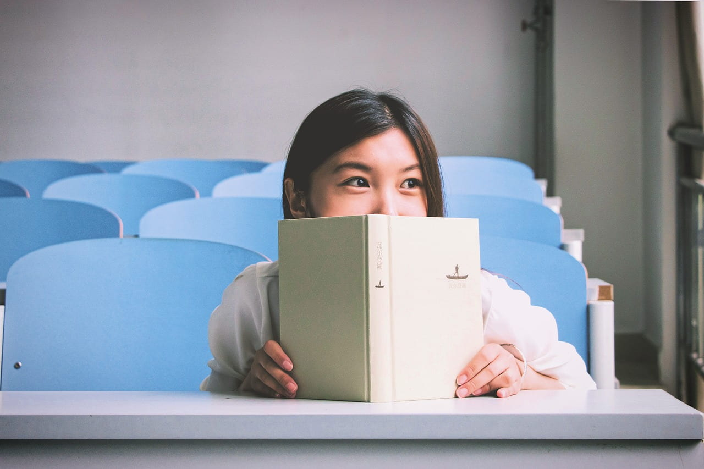 講義室の椅子に座り、机の上で本を読みながら周りの様子をうかがう女の子