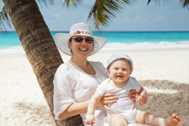 ヤシの木にもたれかかり真っ白な砂浜に座る小さな赤ちゃんを抱いた優しさあふれる女性
