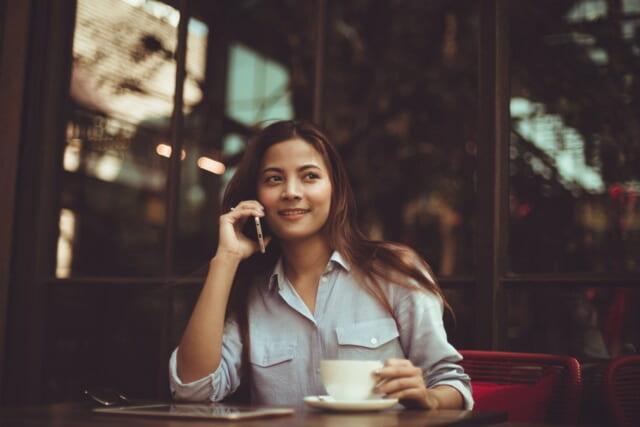コーヒーを飲みながら電話をかけるシンプルでカジュアルながらもシャツをきれいに着こなす清潔感ふれる女性