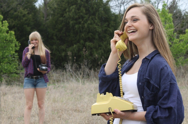 草むらで電話機を抱えながら受話器を耳に当てながら楽しく会話する2人の女の子