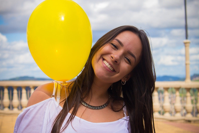 黄色い風船を持ち、にっこりと柔らかく微笑む女の子