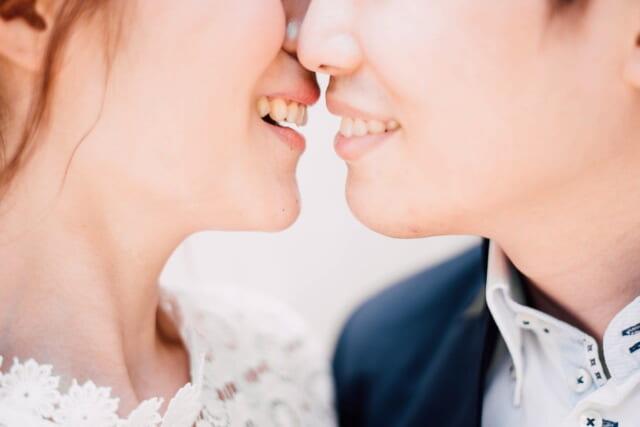 笑顔で口元を寄せ合う幸せそうな花嫁と花婿