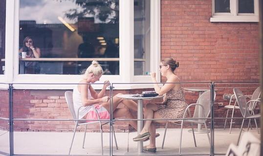 カフェのテラス席で向かい合って座り談笑する2人の女の子