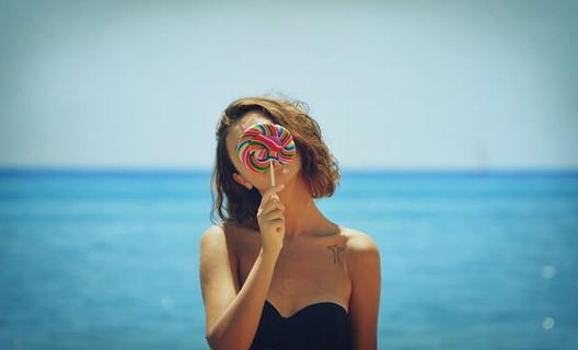 青い海を背に大きなキャンディーで顔を隠しながら首をかしげる女性