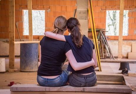 アトリエのベンチに座り肩を寄せ合う仲良しの女の子2人