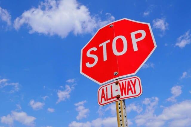 真っ青な空に向かって立つ赤いSTOPの標識