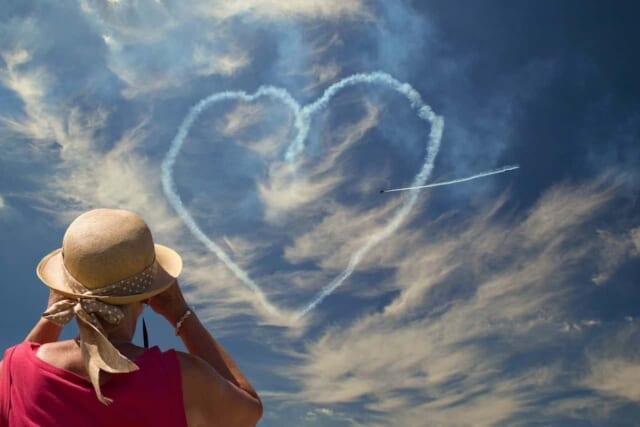 青空に描かれたハート型の飛行機雲とそれを双眼鏡で眺めるピンク色の服の女性
