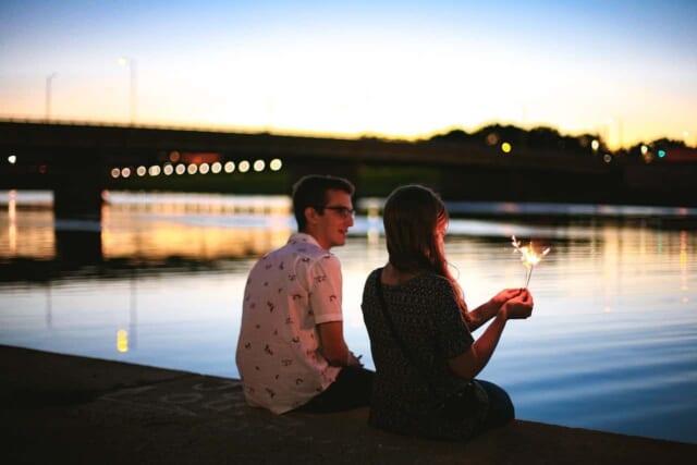 夕日が沈みゆく海と防波堤に坐って楽しそうに花火をするカップル