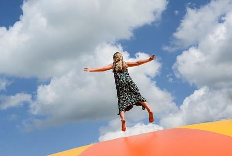 白い雲が広がる青空へ向かって手をあげてジャンプする女の子