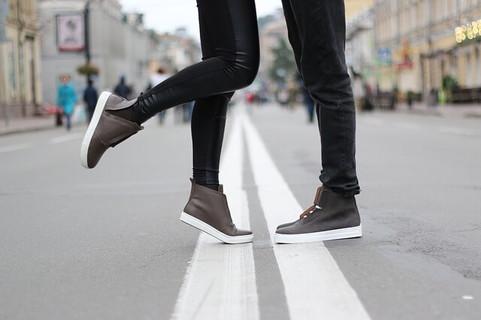 道端でハグをするお揃いのスニーカーを履いたカップルの足元