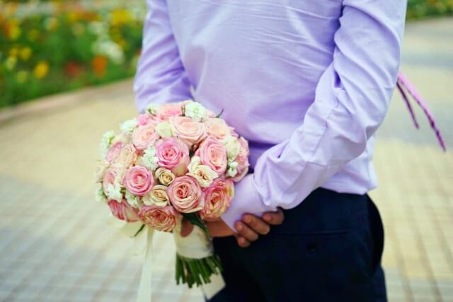 白とピンクの花束を背中に隠して歩く男性