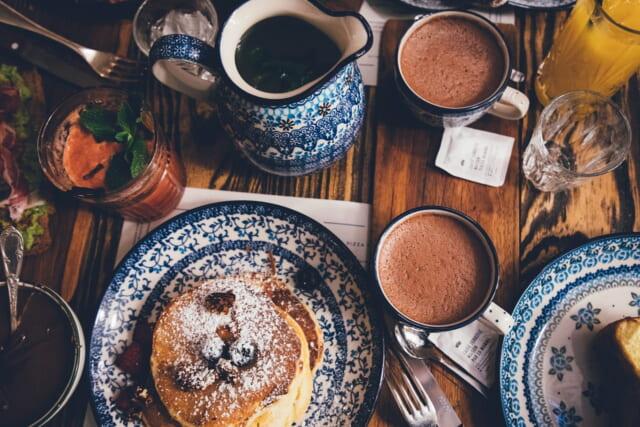 青い食器とパンケーキやホットチョコレートが並んだインスタ映えする食卓
