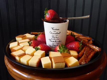 白いカップに入ったチョコレートとお皿にたっぷりと盛られたフォンデュ用のケーキやイチゴ