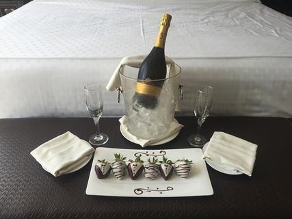 ホテルの部屋に用意された真っ白なシーツのベッド、キンキンに冷やされたシャンパンとグラス、チョコレートでコーティングされたイチゴ