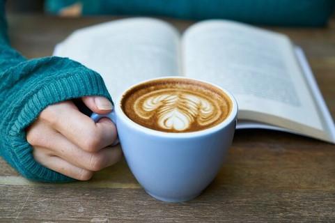 コーヒーを飲みながら読書にひたる女性の手元