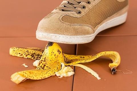 石畳の上に落ちているバナナを今にも踏みそうなベージュのスニーカー