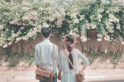 2人仲良く並んで花を眺めるデート中のカップル
