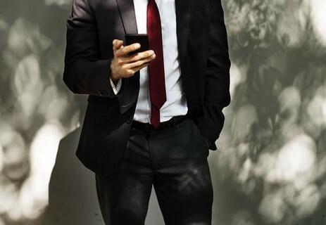 スマートフォンを片手にたたずむスーツをビシッと着こなした男性