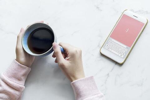 テーブルの上に載ったコーヒーの入ったカップを持つ女性の手とピンク色の画面のスマートフォン