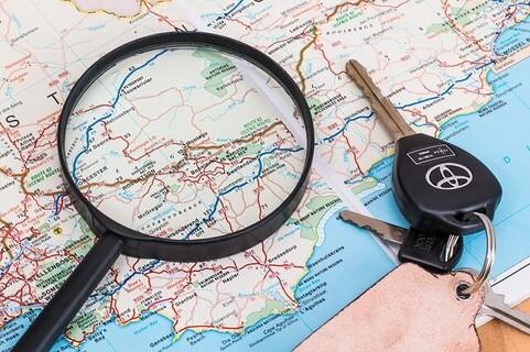 地図の上に置かれた黒い虫メガネと車のキー