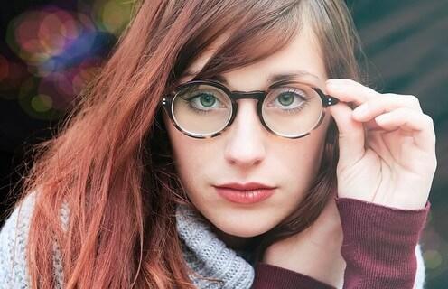 丸いメガネに手をかけカメラにジッと目線を向けるキレイな顔立ちの女の子
