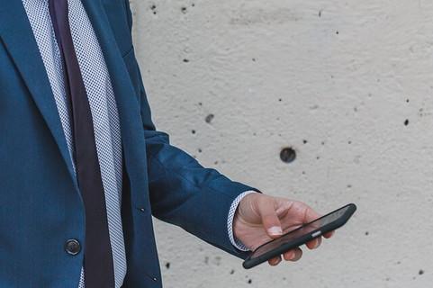 ブルーグレーのスーツを着てスマートフォンを眺める男性
