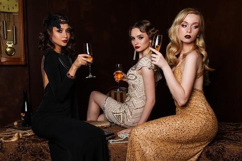 お酒の入ったグラスを片手に腰をかけるドレスとメイクをバッチリ決めた女の子たち