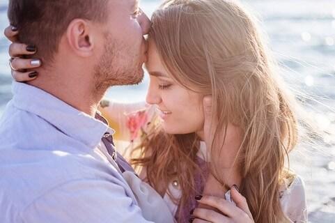 海辺で向かい合い女性の額にキスをする幸せそうな男性